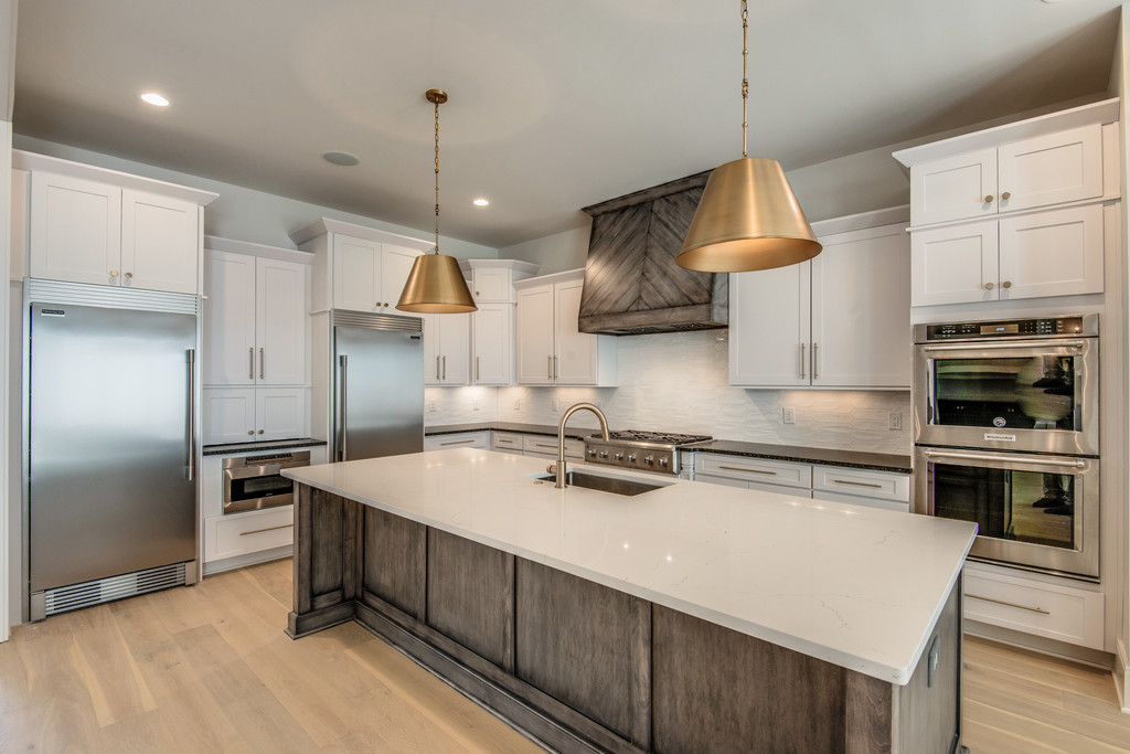 Beautiful kitchen with hanging lights and an island for a new construction home in Brentwood TN new homes from a Nashville Home Builder